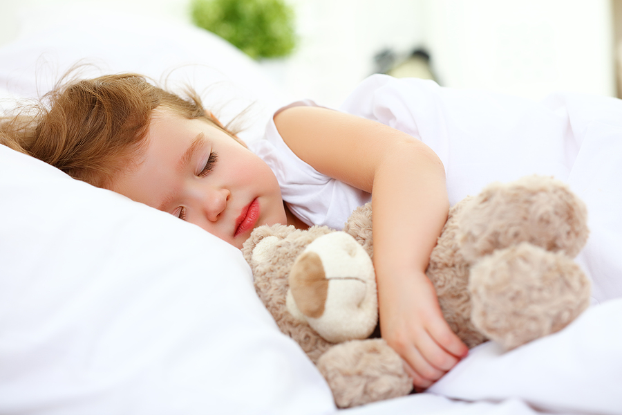 Girl sleeps with teddy bear