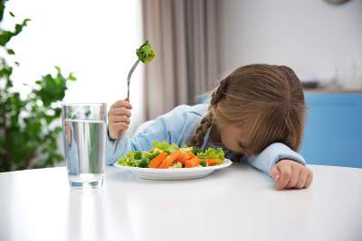 girl refusing to eat vegetables